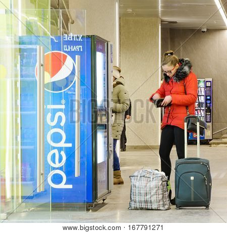 MOSCOW, RUSSIA - JANUARY 31, 2017: Girl Buying drink at the Pepsi Cola vending machine in Leningradsky railway station. Pepsi is a carbonated soft drink that is produced and manufactured by PepsiCo.