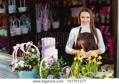 Positive flower shop owner looking at camera and smiling. Small business owner