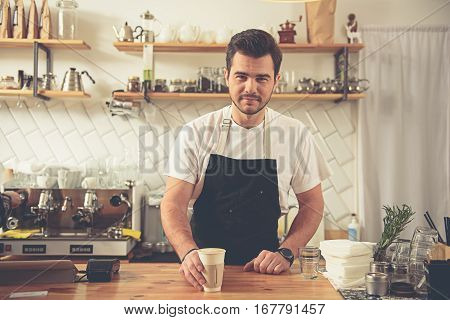 Outgoing barista keeping plastic cup of latte in hand while standing at bar counter. His colleague preparing macchiato behind him