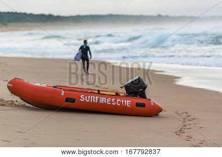 Lifesaver Boat On Sore With Surfer Walking In The Distance