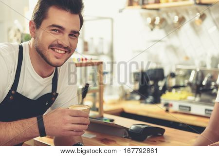 Cheerful worker drinking glass of latte while standing near cash desk. Various appliances are around waiter and barista in confectionary