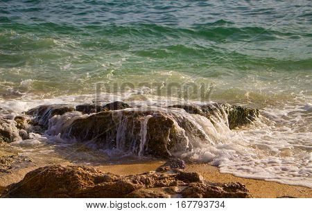 Green sea water surf over beach stone. Tropical island seaside abstract photo. Sunny day on beach. Cool seawater wave splashes on coast. Exotic island vacation banner template. Relaxing marine photo