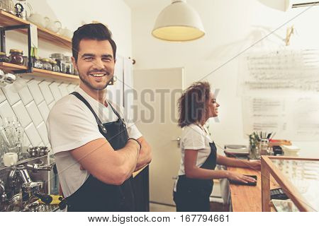 Laughing handsome man standing near coffee machine in cosy cafeteria. Smiling woman cleaning stand while leaning on it