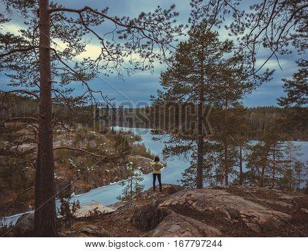 girl photographer on the cliff , Karelian isthmus, Russia