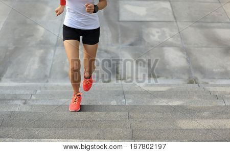 young sport woman running upstairs on city stairs