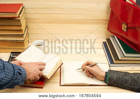 Financial concept. Business partners discuss profit and losses analyzing financial results. On a wooden table books documents calculator stapler red briefcase.