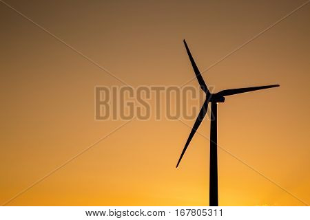This wind turbine spins as the sun sets.