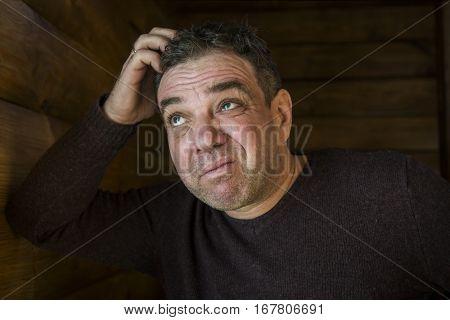 Sad man portrait. He scratches his head