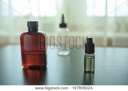 The Bottle Of Flavor For Personal Vaporiser And Other Bottles Stand On A Black Wooden Table.