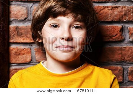 Portrait of a cute nine year old boy leaning against the brick wall. Clothes for children. Kid's fashion.