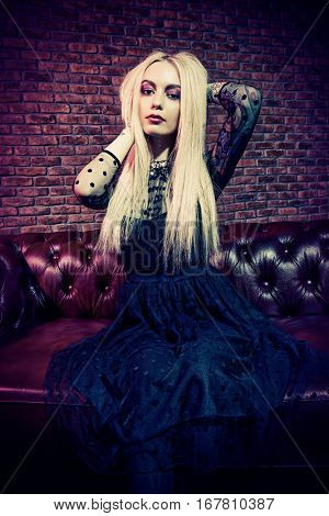 Portrait of an extravagant attractive woman with bright make-up and long blonde hair. Beauty, fashion concept. Cosmetics, make-up. Gothic style.