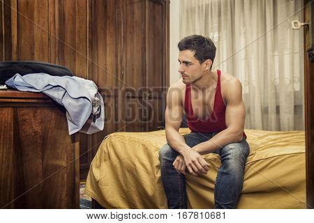 Handsome young man sitting on his bed with serious expression, staring in the void with a blank look
