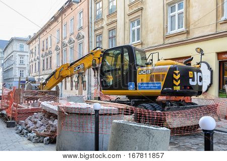 Ukraine Lviv - December 17 2016: Repair of the aqueduct in the city center of Lviv on the narrow street. Construction machinery. Excavation work at the construction site.