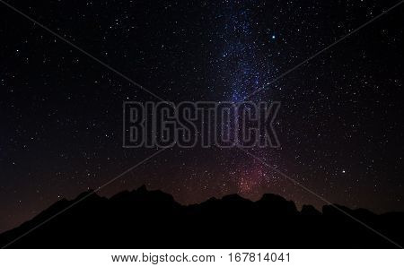 Silhouette mountain peak at night with sky full of stars and milky way