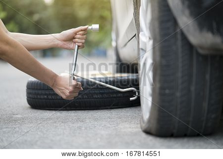 young woman changing wheel on a roadside