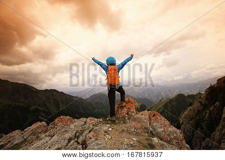 successful woman hiker open arms on mountain peak cliff