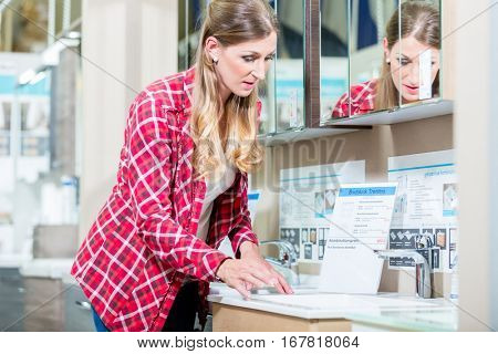 Woman in sanitary goods department of hardware store looking at lavatory