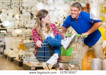 Man pushing woman in shopping cart trough electric goods department of hardware store