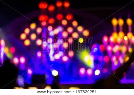 Abstract background with defocused bokeh of laser show in modern disco party night club - Concept of nightlife with music and entertainment - Image with powered colored halos and vivid bright lights