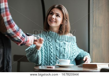 Image of happy young woman dressed in sweater sitting in cafe at cold winter day and pays for her order with debit card. Look aside.