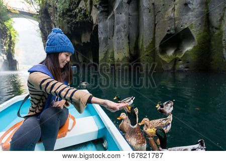 Woman feeding duck and travel on boat in Takachiho gorge