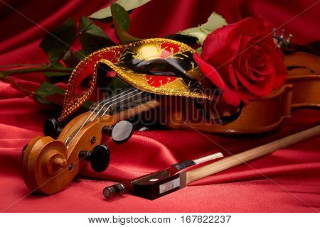 Violin (fiddle), theater mask and red rose lying on the perfect red satin fabric. String instrument.