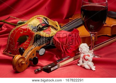 Violin (fiddle), theater mask, glass of wine and red rose lying on the perfect red satin fabric. String instrument. Valentine's day.