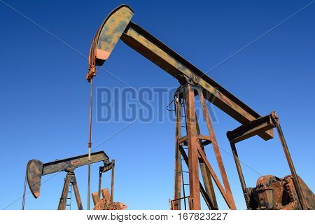 Rusty Oilfield Pumpjack (rocking horse) over a wellhead. Clear blue sky.