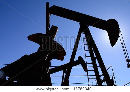 Oilfield pumpjack rusty and old silhouetted by the sun.