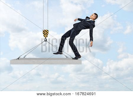 Businessman falling from the concrete slab suspended on the construction crane hook. Business and success. Building and construction. Balancing in the market. Balancing gains and losses.