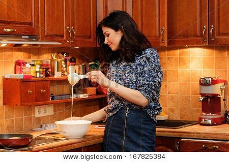 Young woman making pancakes at home