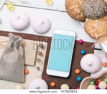 Smartphone among sweets on the table. Clipping path