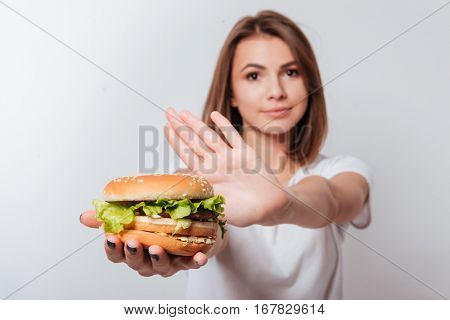 Image of serious young woman standing over white background while showing fastfood to camera
