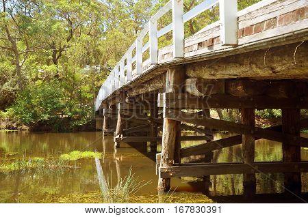 Historic wooden Varney Bridge across Kangaroo Creek at Audley, Royal National Park, Sydney, Australia. Retro toned. Underneath perspective.