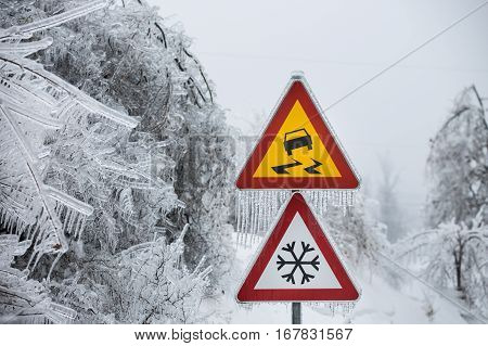 Dangerous and icy road sign with sleet covered trees. Danger on the road black ice danger wintertime concept.