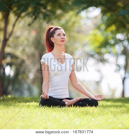 Pretty woman doing yoga exercises in the park. Beauty nature scene with colorful background at spring season. Outdoor lifestyle. Happy woman relax on green grass