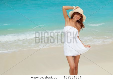 Fashion woman walking on the beach. Happy lifestyle. White sand and crystal blue sea of tropical beach. Vacation at Paradise. Ocean beach relax, travel to islands
