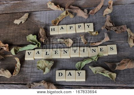 Happy Valentines day wording by crossword on old wooden board background