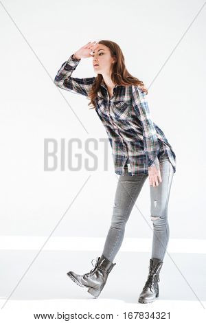 Full length of pretty young woman standing and looking far away over white background