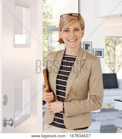 Happy casual caucasian blonde businesswoman standing at home doorway, wearing glasses, folder in hand. Smiling, standing, looking at camera.