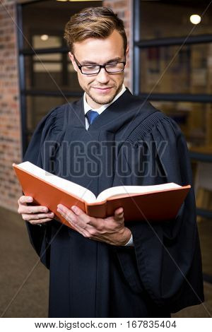 Lawyer reading law book near library in office