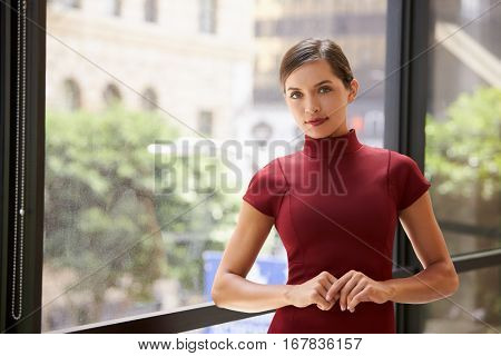 Young white businesswoman leaning by a window at work