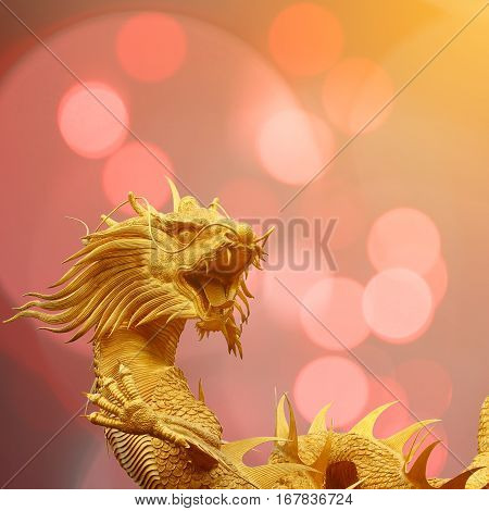 Golden chinese dragon statue with blurry bokeh background.