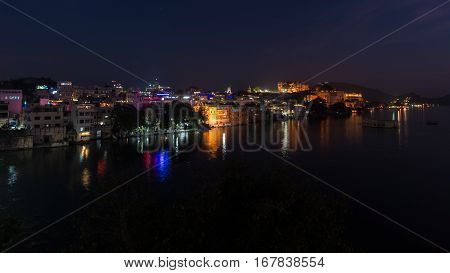Glowing Cityscape At Udaipur By Night. The Majestic City Palace Reflecting Lights On Lake Pichola, T