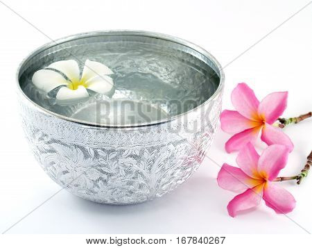 silver water bowl with floating flower and placed beside on white background, containers for scoop water that used in the past.currently used as decorative Asian style or in religious ceremonies