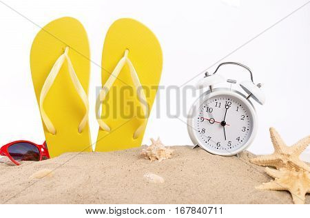 Yellow beach slippers with white vintage alarm clock sunglasses and seashells in the sand on a white background. Summer background