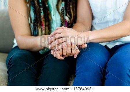 Lesbian couple sitting on sofa and holding hands