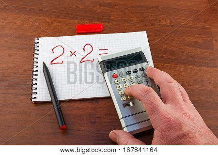 Man's hand pushes the button on the calculator solving the equation
