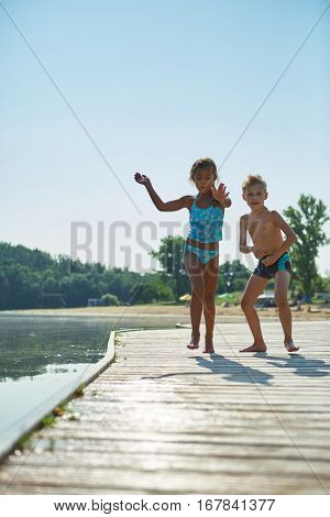 Two children playing on a pier at the lake in summer