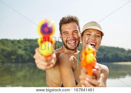 Couple with squirt guns laughing happily in summer